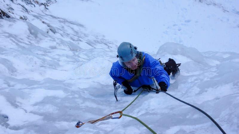 Αρσενικός ορειβάτης πάγου σε μια μπλε ζακέτα σε έναν απότομο παγωμένο καταρράκτη το βαθύ χειμώνα στις Άλπεις της Ελβετίας στοκ φωτογραφία με δικαίωμα ελεύθερης χρήσης