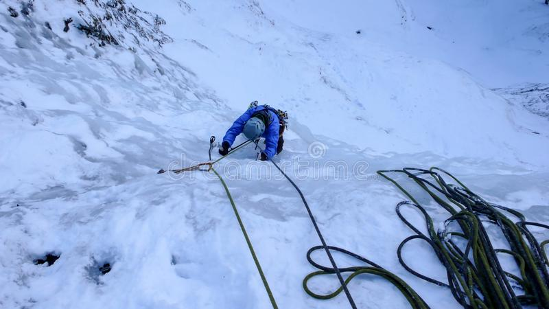 Αρσενικός ορειβάτης πάγου σε μια μπλε ζακέτα σε έναν απότομο παγωμένο καταρράκτη το βαθύ χειμώνα στις Άλπεις της Ελβετίας στοκ εικόνα