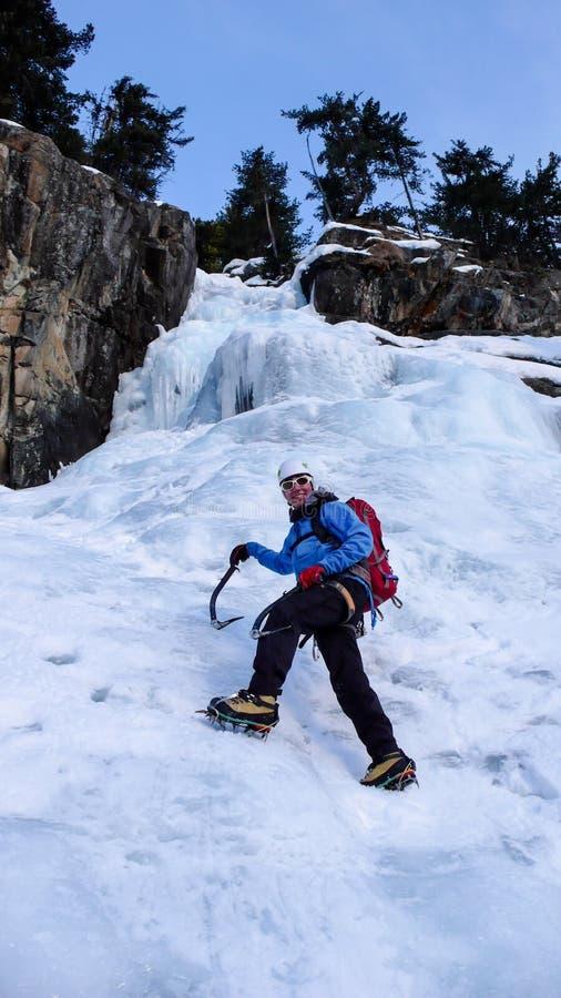 Αρσενικός ορειβάτης πάγου σε μια μπλε ζακέτα σε έναν πανέμορφο παγωμένο καταρράκτη που αναρριχείται στις Άλπεις το βαθύ χειμώνα στοκ φωτογραφία με δικαίωμα ελεύθερης χρήσης