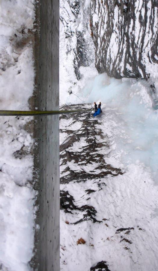 Αρσενικός ορειβάτης πάγου σε μια μπλε ζακέτα που το α από ένα κιγκλίδωμα γεφυρών επάνω σε έναν κάθετο παγωμένο καταρράκτη στοκ εικόνες