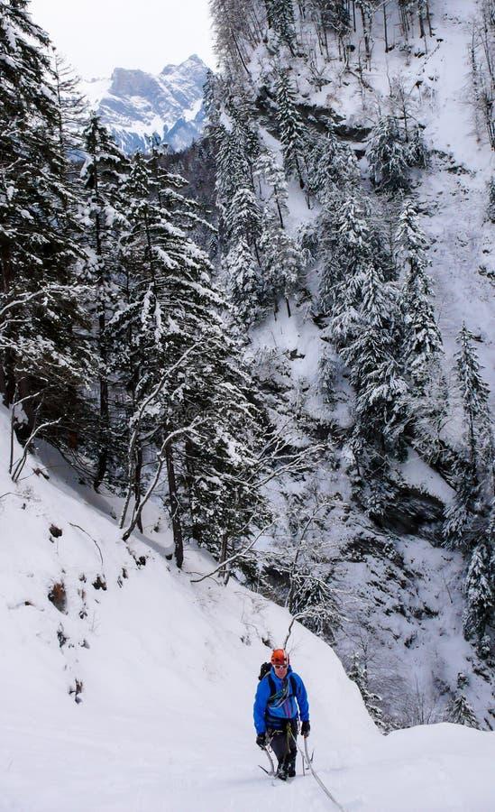Αρσενικός ορειβάτης πάγου σε μια παγωμένη παγόπτωση που καλύπτεται στο βαθύ χιόνι στοκ φωτογραφία με δικαίωμα ελεύθερης χρήσης