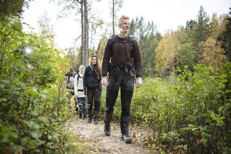 Αρσενικός οδοιπόρος με τους φίλους που περπατούν στο δασικό ίχνος στοκ φωτογραφίες
