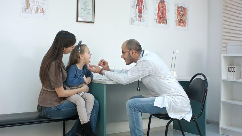 Αρσενικός παιδίατρος που εξετάζει το λαιμό της συνεδρίασης μικρών κοριτσιών με τη μητέρα της στοκ εικόνα με δικαίωμα ελεύθερης χρήσης