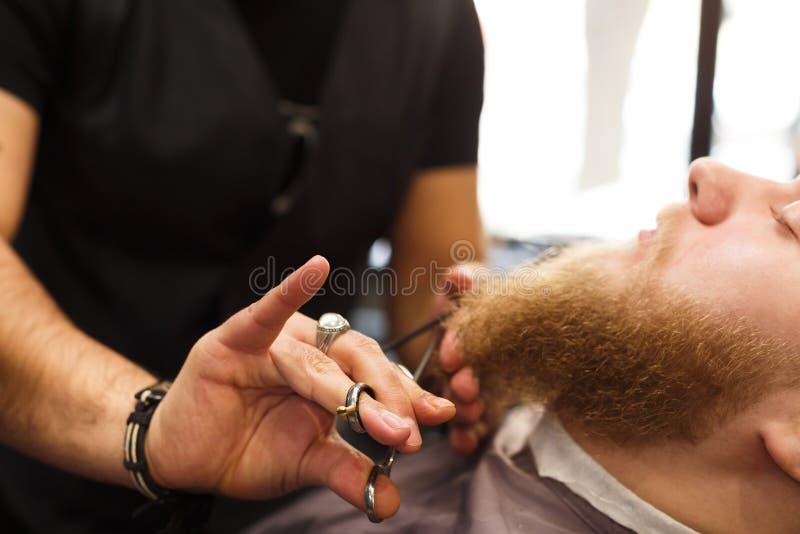 Αρσενικός πελάτης που έχει το κούρεμα γενειάδων στο barbershop στοκ φωτογραφία με δικαίωμα ελεύθερης χρήσης