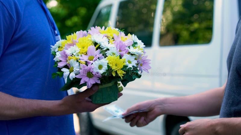Αρσενικός πληρώνοντας αγγελιαφόρος για την παράδοση λουλουδιών, επέτειος παρούσα, δώρο γενεθλίων στοκ φωτογραφία με δικαίωμα ελεύθερης χρήσης