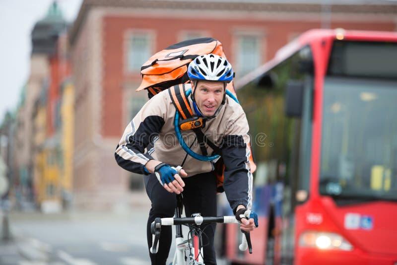 Αρσενικός ποδηλάτης με την οδήγηση τσαντών παράδοσης αγγελιαφόρων στοκ εικόνες