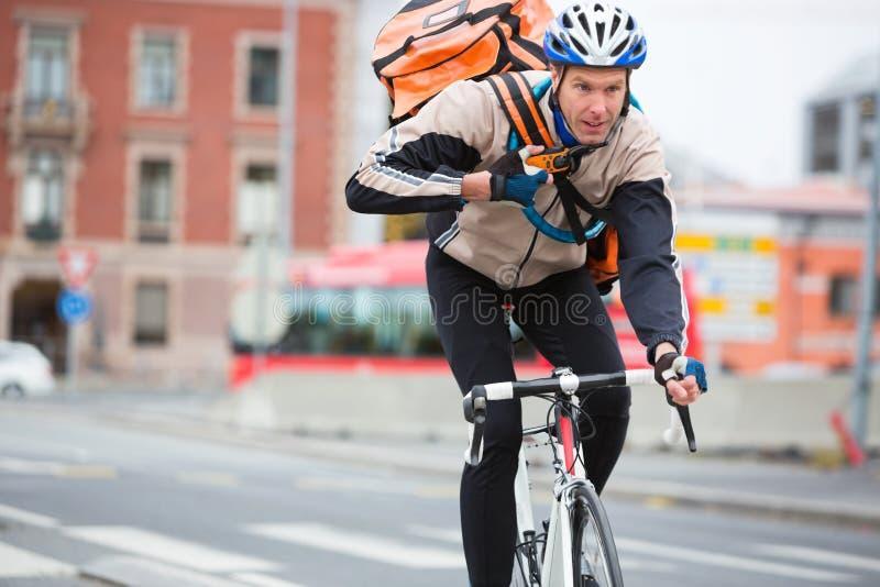 Αρσενικός ποδηλάτης με την οδήγηση τσαντών παράδοσης αγγελιαφόρων στοκ εικόνα με δικαίωμα ελεύθερης χρήσης