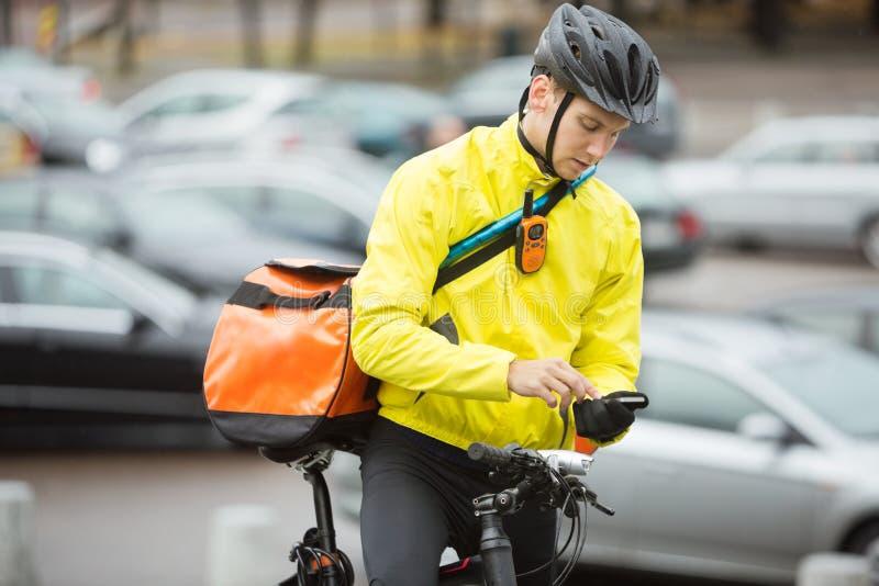Αρσενικός ποδηλάτης με την τσάντα αγγελιαφόρων που χρησιμοποιεί το κινητό τηλέφωνο στοκ εικόνες