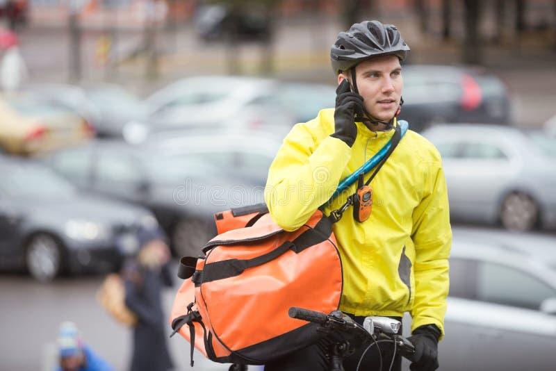 Αρσενικός ποδηλάτης με την τσάντα αγγελιαφόρων που χρησιμοποιεί το κινητό τηλέφωνο στοκ εικόνα