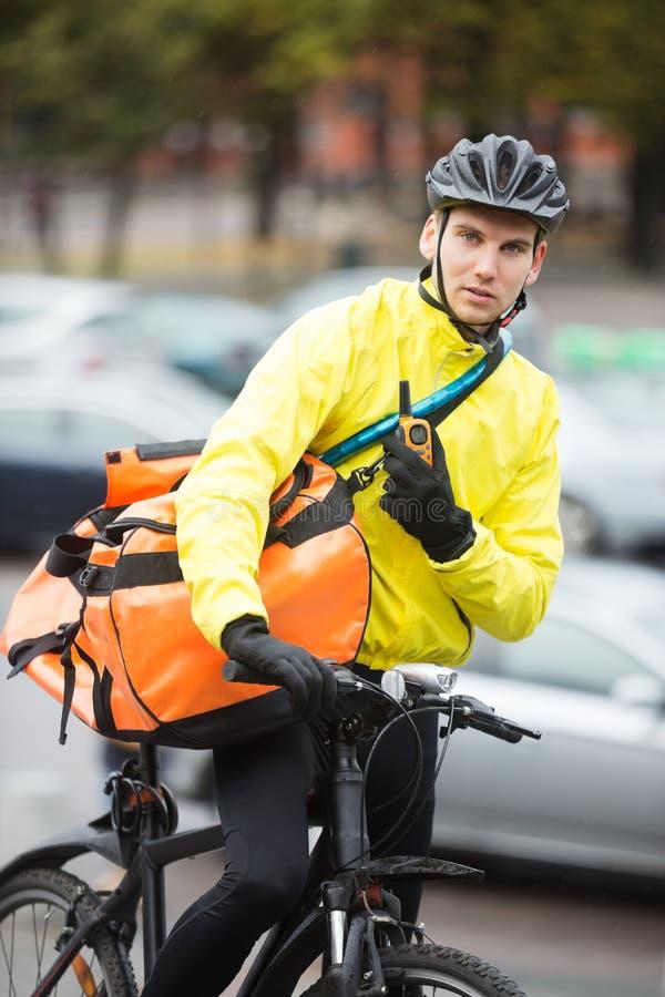 Αρσενικός ποδηλάτης με την τσάντα αγγελιαφόρων που χρησιμοποιεί Walkie-Talkie στοκ φωτογραφία