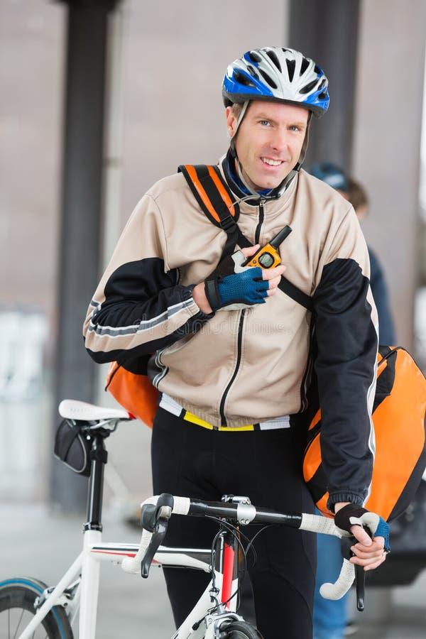 Αρσενικός ποδηλάτης με την τσάντα αγγελιαφόρων που χρησιμοποιεί Walkie-Talkie στοκ φωτογραφία με δικαίωμα ελεύθερης χρήσης
