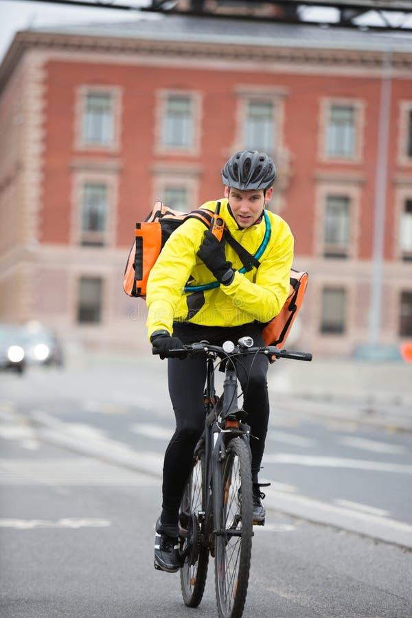 Αρσενικός ποδηλάτης με την τσάντα αγγελιαφόρων που χρησιμοποιεί Walkie-Talkie στοκ φωτογραφίες
