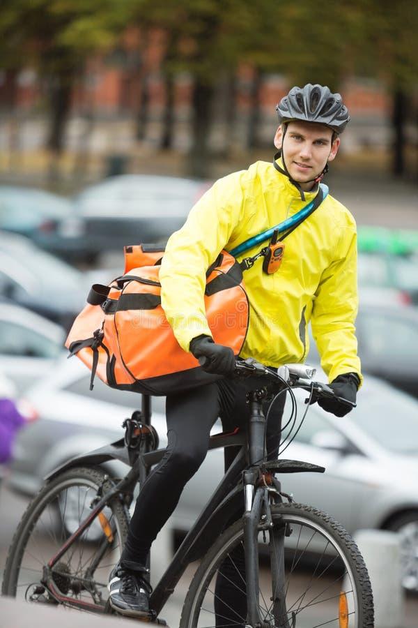 Αρσενικός ποδηλάτης με την τσάντα παράδοσης αγγελιαφόρων στην οδό στοκ εικόνες