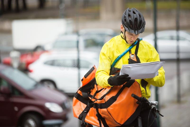 Αρσενικός ποδηλάτης με την τσάντα συσκευασίας και αγγελιαφόρων επάνω στοκ εικόνα