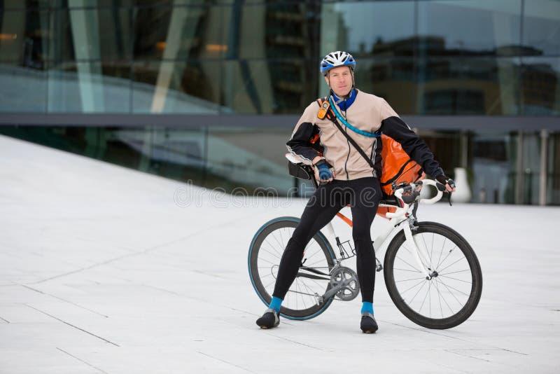 Αρσενικός ποδηλάτης με τη συνεδρίαση τσαντών αγγελιαφόρων στο ποδήλατο στοκ εικόνες