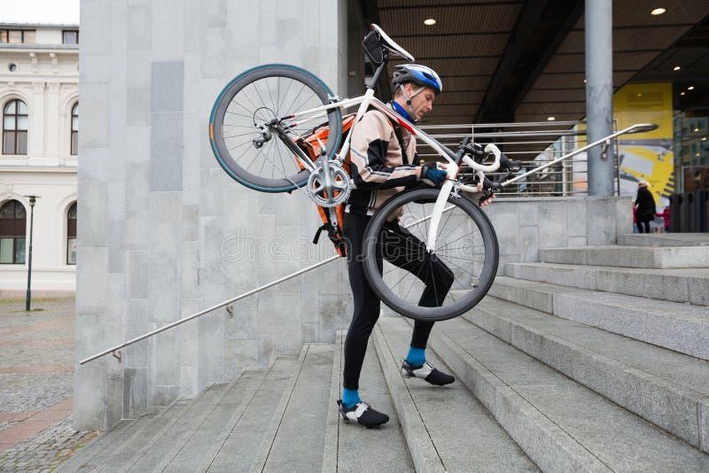 Αρσενικός ποδηλάτης με το ποδήλατο στο περπάτημα ώμων του στοκ εικόνα με δικαίωμα ελεύθερης χρήσης