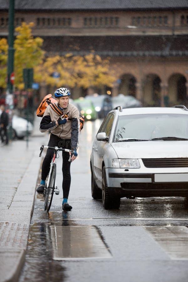 Αρσενικός ποδηλάτης με το σακίδιο πλάτης που χρησιμοποιεί Walkie-Talkie επάνω στοκ φωτογραφία