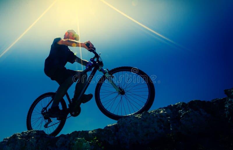 Αρσενικός ποδηλάτης σε ένα ποδήλατο βουνών, αναδρομικά φωτισμένο στοκ φωτογραφίες