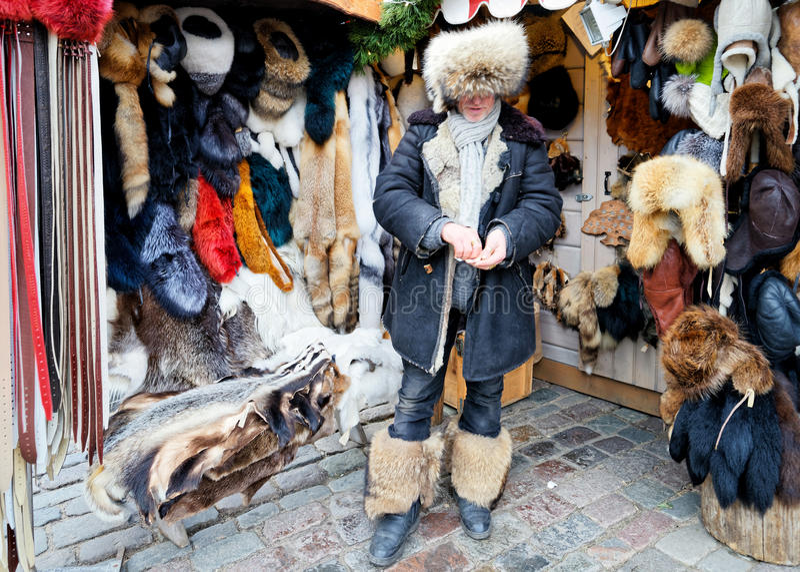 Αρσενικός πωλητής των στοιχείων γουνών στην αγορά Χριστουγέννων στη Ρήγα στοκ εικόνα