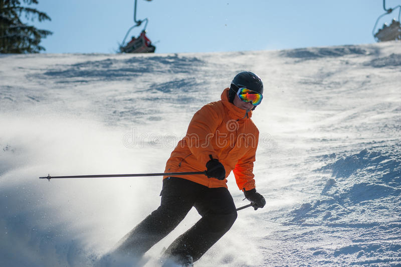 Αρσενικός σκιέρ που κάνει σκι προς τα κάτω στο χιονοδρομικό κέντρο ενάντια στον ανελκυστήρα στοκ εικόνα με δικαίωμα ελεύθερης χρήσης