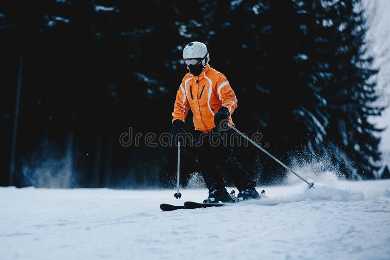 Αρσενικός σκιέρ σε μια κλίση στα βουνά Παγωμένο σκοτεινό δάσος στο β στοκ φωτογραφία