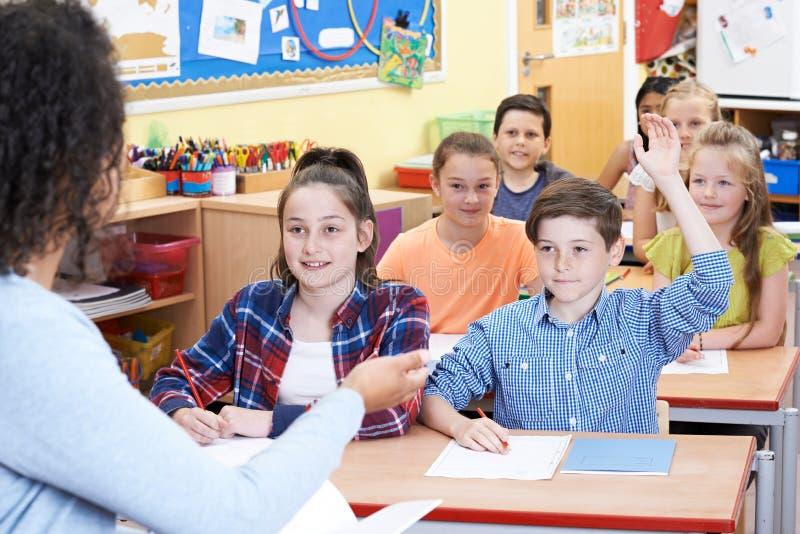 Αρσενικός στοιχειώδης μαθητής που απαντά στην ερώτηση στην κατηγορία στοκ εικόνες