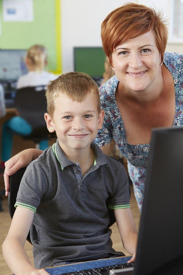 Αρσενικός στοιχειώδης μαθητής στην κατηγορία υπολογιστών με το δάσκαλο στοκ εικόνα