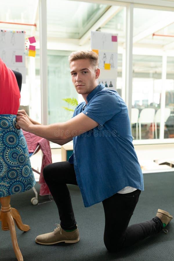 Αρσενικός σχεδιαστής μόδας που ντύνει ένα μανεκέν στο στούντιο σχεδίου στοκ φωτογραφίες