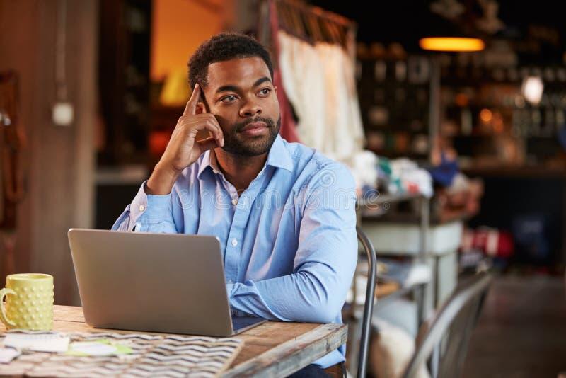 Αρσενικός σχεδιαστής μόδας που εργάζεται στο lap-top στο στούντιο στοκ φωτογραφία με δικαίωμα ελεύθερης χρήσης