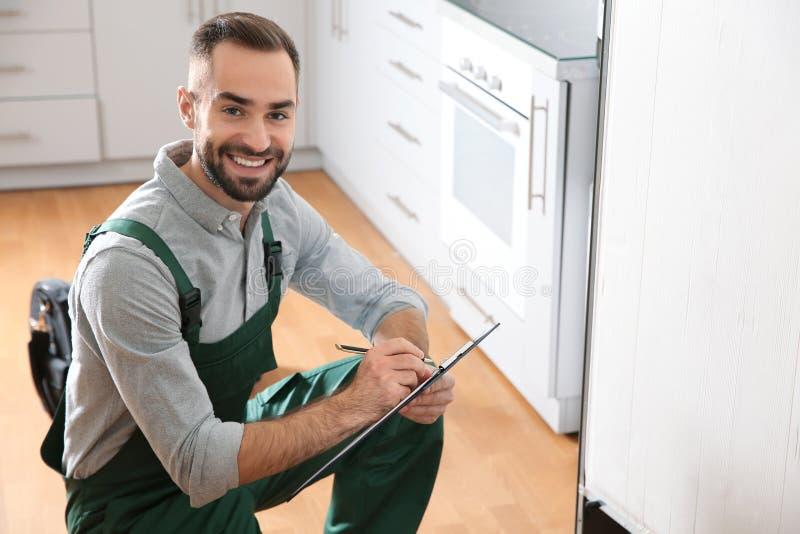 Αρσενικός τεχνικός με την περιοχή αποκομμάτων που εξετάζει το ψυγείο στοκ εικόνες με δικαίωμα ελεύθερης χρήσης