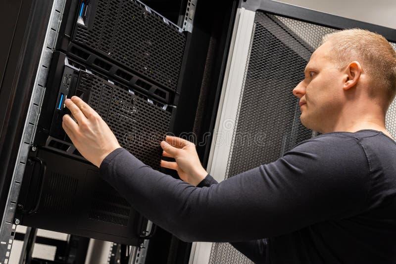 Αρσενικός τεχνικός που εργάζεται με τους κεντρικούς υπολογιστές σε Datacenter στοκ φωτογραφία με δικαίωμα ελεύθερης χρήσης
