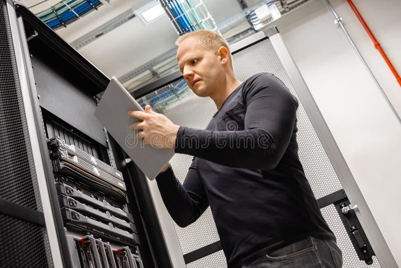 Αρσενικός τεχνικός που χρησιμοποιεί την ψηφιακή ταμπλέτα σε Datacenter για να ελέγξει το SAN και τους κεντρικούς υπολογιστές στοκ εικόνα