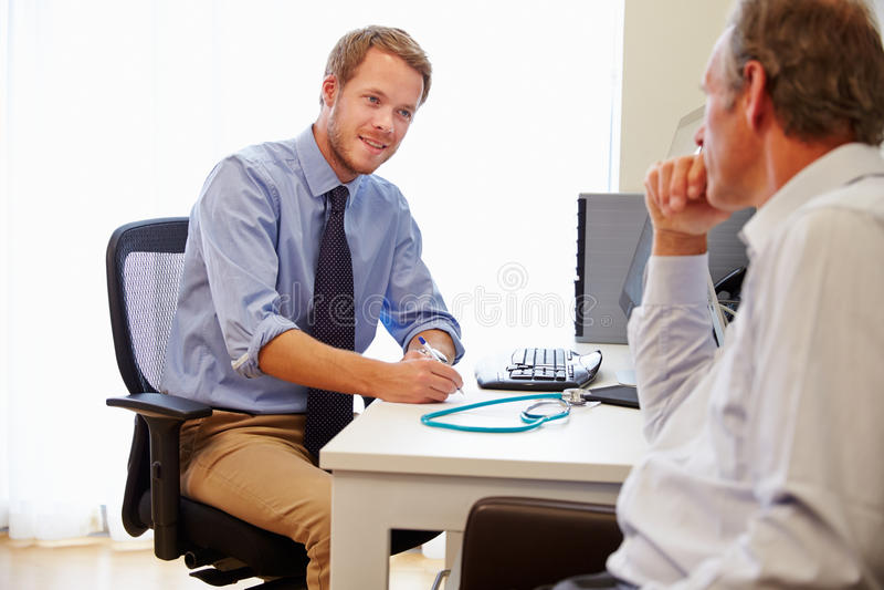 Αρσενικός υπομονετικός διοργανώνοντας τις διαβουλεύσεις με το γιατρό στην αρχή στοκ εικόνες