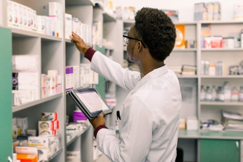 Αρσενικός φαρμακοποιός αφροαμερικάνων που χρησιμοποιεί την ψηφιακή ταμπλέτα κατά τη διάρκεια του καταλόγου στο φαρμακείο στοκ φωτογραφία με δικαίωμα ελεύθερης χρήσης