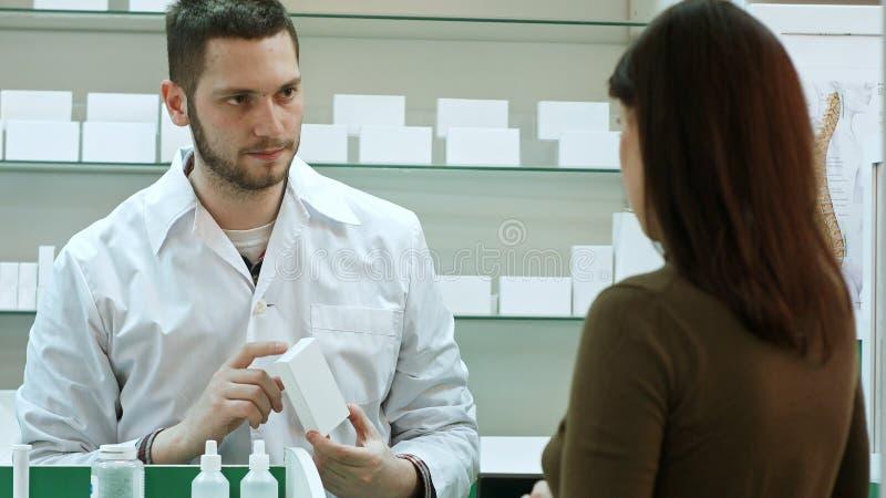 Αρσενικός φαρμακοποιός και θηλυκός πελάτης στο φαρμακείο στοκ εικόνα