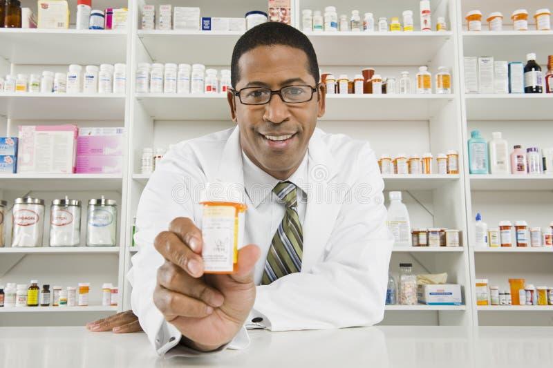 Αρσενικός φαρμακοποιός που εργάζεται στο φαρμακείο στοκ φωτογραφία