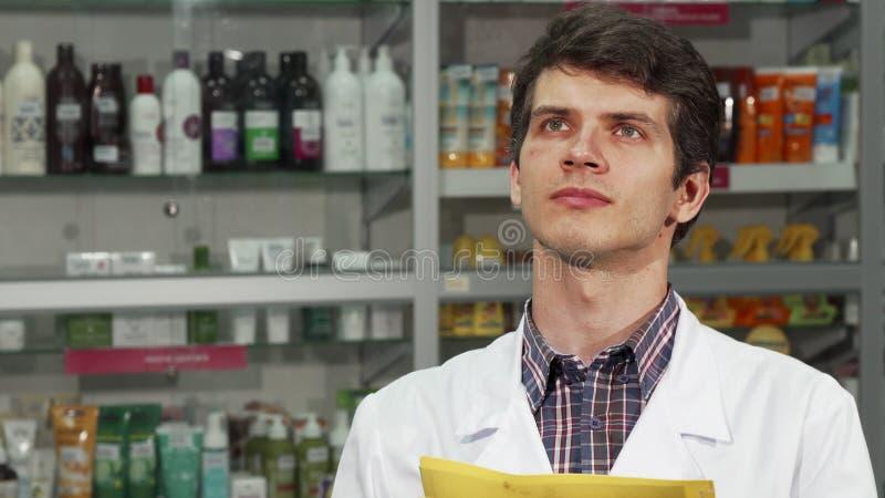 Αρσενικός φαρμακοποιός που κάνει τον κατάλογο στο φαρμακείο στοκ φωτογραφία με δικαίωμα ελεύθερης χρήσης