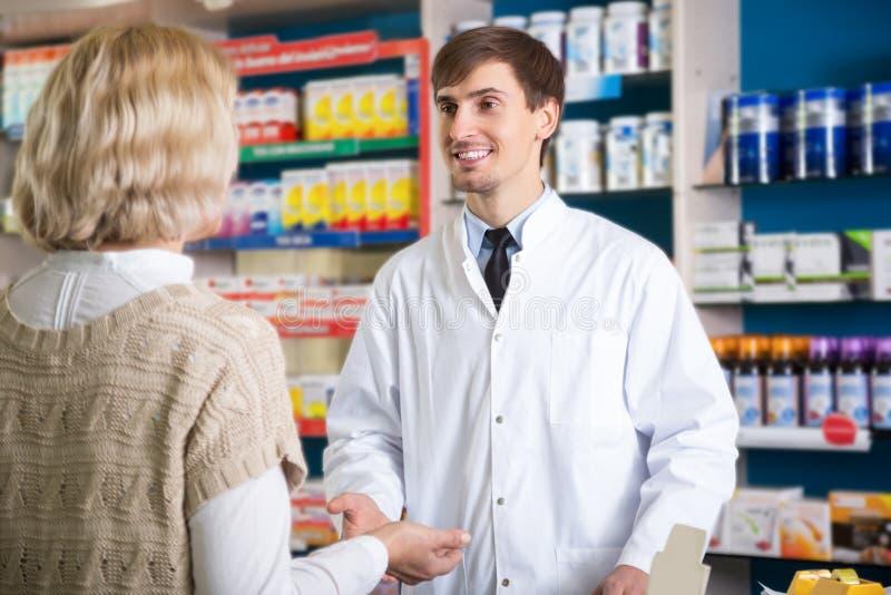 Αρσενικός φαρμακοποιός που μιλά στον πελάτη στο φαρμακείο στοκ εικόνα