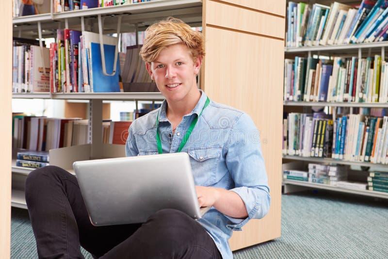 Αρσενικός φοιτητής πανεπιστημίου που μελετά στη βιβλιοθήκη με το lap-top στοκ εικόνες