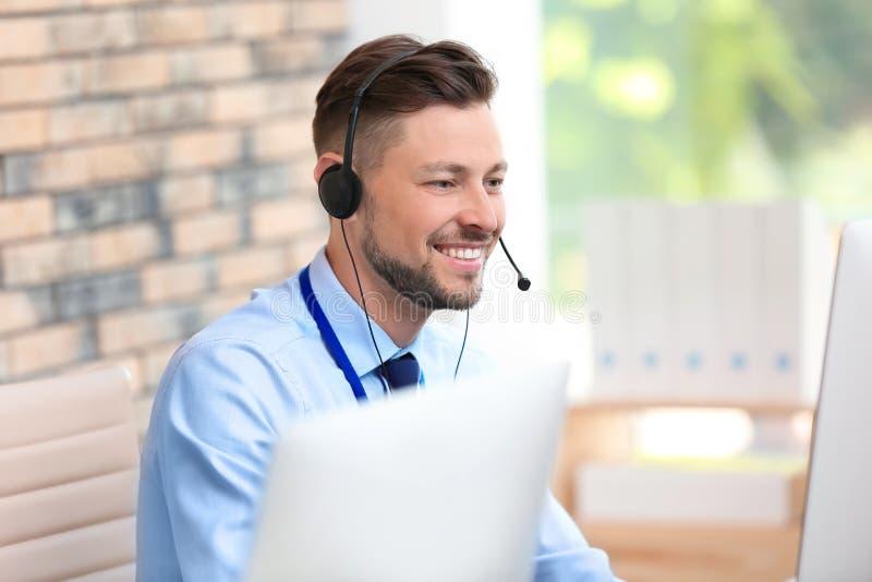 Αρσενικός χειριστής τεχνικής υποστήριξης με τον εργασιακό χώρο κασκών στοκ εικόνα