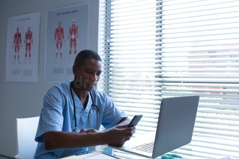 Αρσενικός χειρούργος που χρησιμοποιεί το κινητό τηλέφωνο στο γραφείο στοκ φωτογραφίες με δικαίωμα ελεύθερης χρήσης