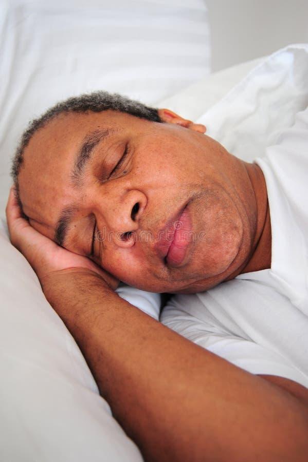Αρσενικός ύπνος αφροαμερικάνων στο κρεβάτι στοκ εικόνες με δικαίωμα ελεύθερης χρήσης