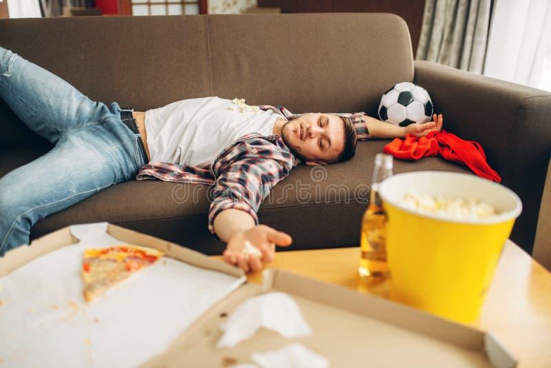 Αρσενικός ύπνος οπαδών ποδοσφαίρου στον καναπέ στο σπίτι στοκ εικόνα με δικαίωμα ελεύθερης χρήσης