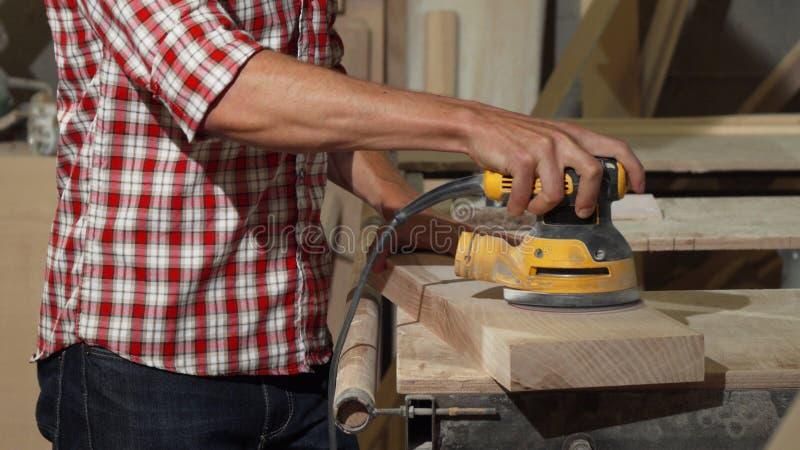 Αρσενικό κομμάτι στίλβωσης ξυλουργών του ξύλου στο εργαστήριό του στοκ εικόνες