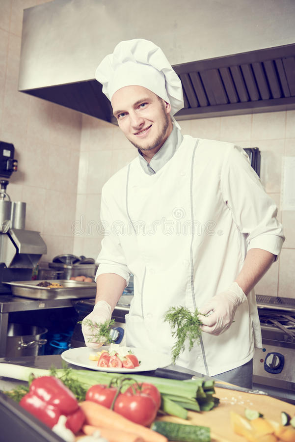 Αρσενικό μαγείρεμα πορτρέτου μαγείρων αρχιμαγείρων στην κουζίνα στοκ εικόνα με δικαίωμα ελεύθερης χρήσης
