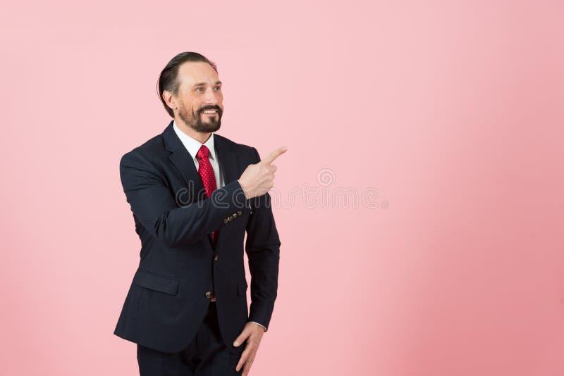 Αρσενικό Μεσαίωνα στο κοστούμι και τον κόκκινο δεσμό που δείχνουν μακριά την πλευρά με το δάχτυλό του στο ρόδινο ροδαλό υπόβαθρο στοκ φωτογραφία