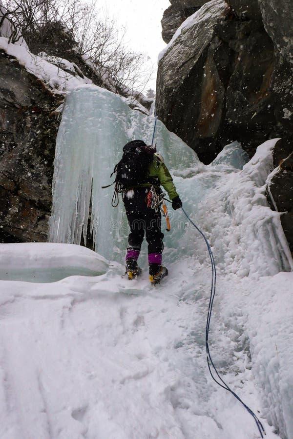 Αρσενικό ορειβατών πάγου σε έναν παγωμένο καταρράκτη στις ελβετικές Άλπεις στοκ φωτογραφία