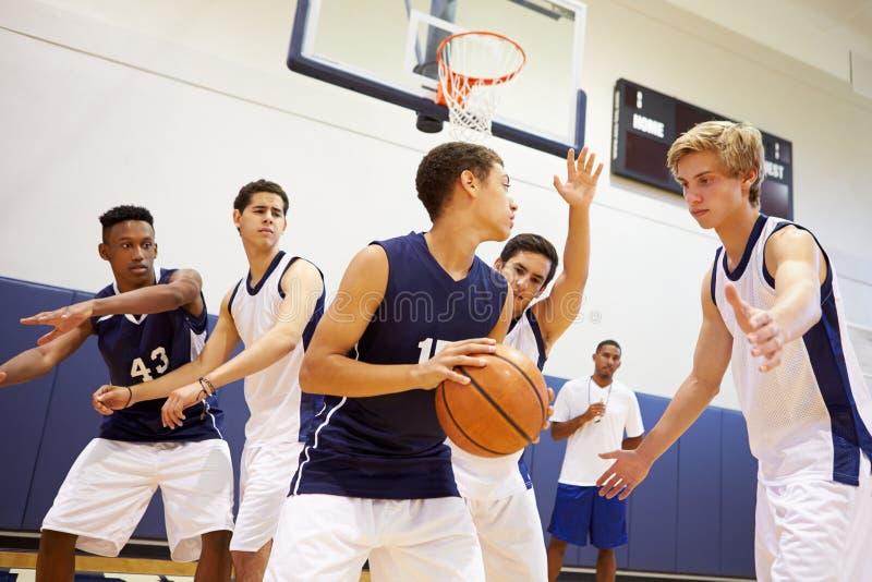 Αρσενικό παίζοντας παιχνίδι ομάδα μπάσκετ γυμνασίου στοκ εικόνες