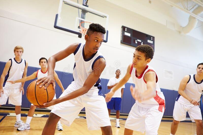 Αρσενικό παίζοντας παιχνίδι ομάδα μπάσκετ γυμνασίου στοκ εικόνα
