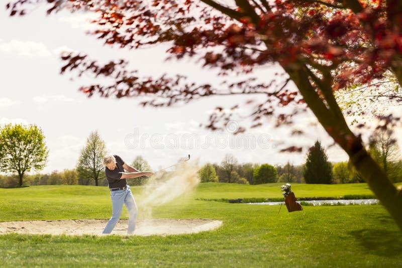 Αρσενικό παιχνίδι παικτών γκολφ από τον κίνδυνο αποθηκών άμμου στοκ εικόνες